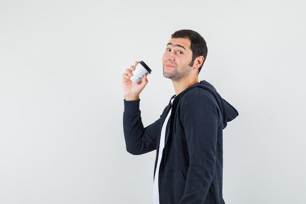 Jonge man met afhaalmaaltijden koffiekopje, glimlachend in wit t-shirt en zwarte hoodie met ritssluiting en op zoek gelukkig, vooraanzicht.