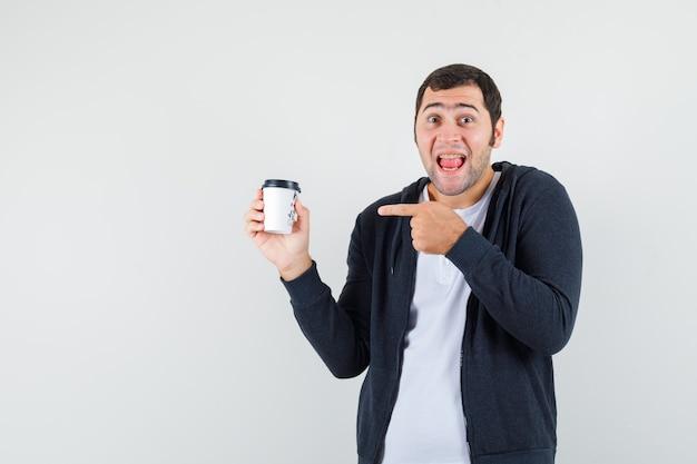 Jonge man met afhaalmaaltijden koffiekopje, wijzend naar het met wijsvinger in wit t-shirt en zwarte hoodie met ritssluiting en op zoek verrast, vooraanzicht.