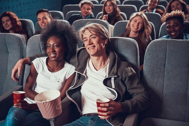 Jonge man met afrikaanse vrouw in de bioscoop