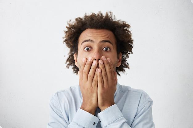 Jonge man met afro kapsel voor mond en camera kijken met bang uitdrukking op zijn gezicht