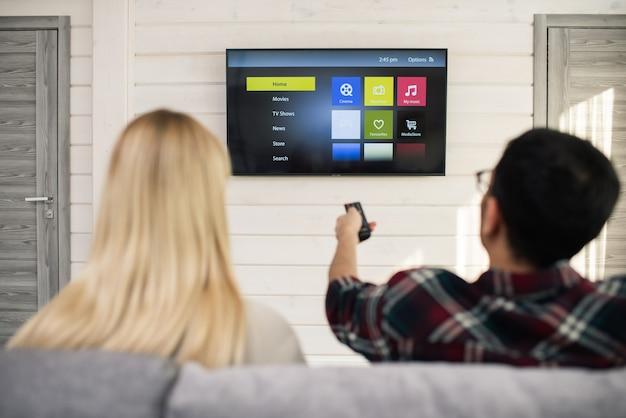 Jonge man met afstandsbediening iets kiezen om naar te kijken terwijl hij voor tv zit met zijn vriendin in de buurt