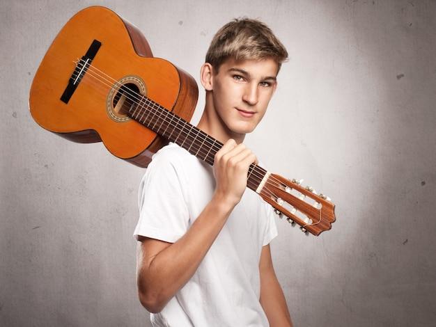 Jonge man met akoestische gitaar op grijs