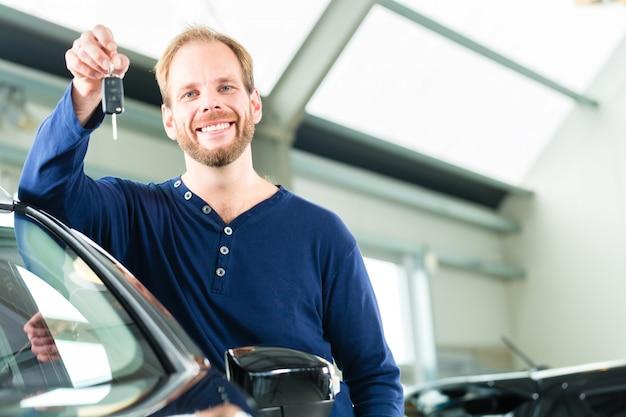 Jonge man met auto in het autohandel drijven