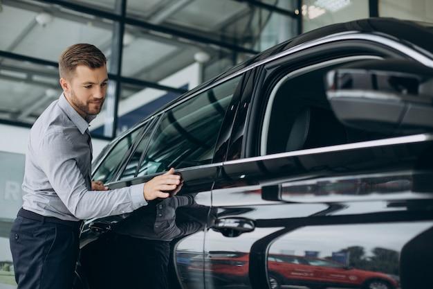 Jonge man met autosleutels bij zijn nieuwe auto