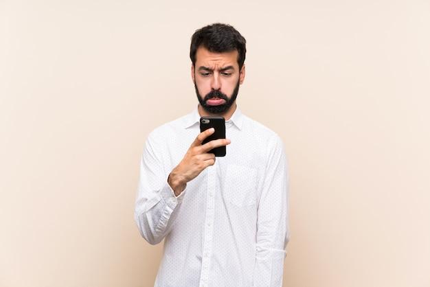Jonge man met baard die mobiel met droevige en depressieve uitdrukking houdt