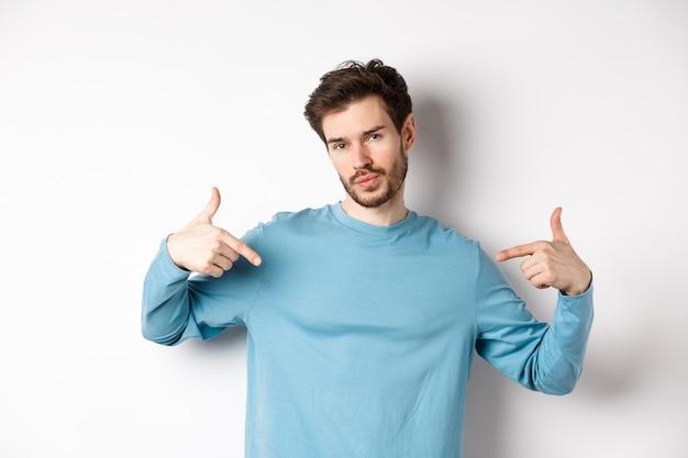 Jonge man met baard die zich zelfverzekerd voelt, naar zichzelf wijst en een zelfvoldaan gezicht trekt, staand op een witte achtergrond koel en brutaal.