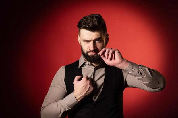 Jonge man met baard in zwarte vest poseren in studio met rode achtergrond. een man maakt zijn snor recht met zijn hand. detailopname