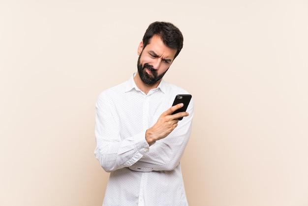 Jonge man met baard met een mobiel gevoel van streek