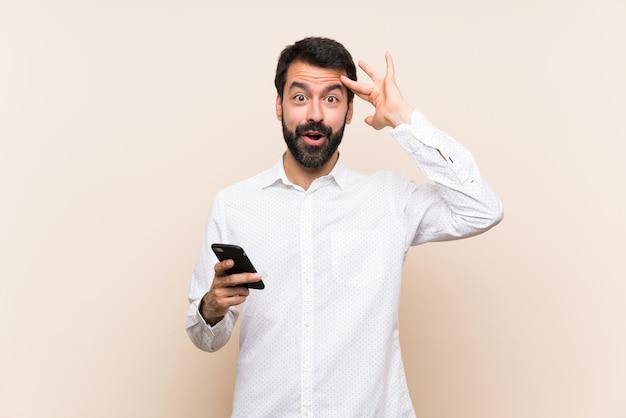 Jonge man met baard met een mobiel heeft zich net iets gerealiseerd en heeft de oplossing voor ogen