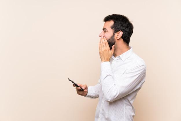 Jonge man met baard met een mobiel schreeuwen met mond wijd open voor de zijtak