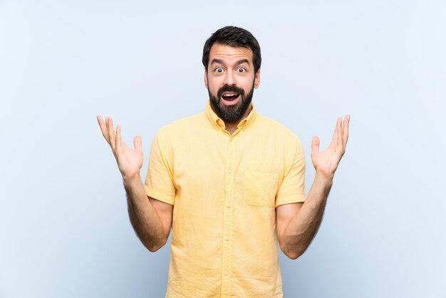 Jonge man met baard op blauw met geschokte gelaatsuitdrukking