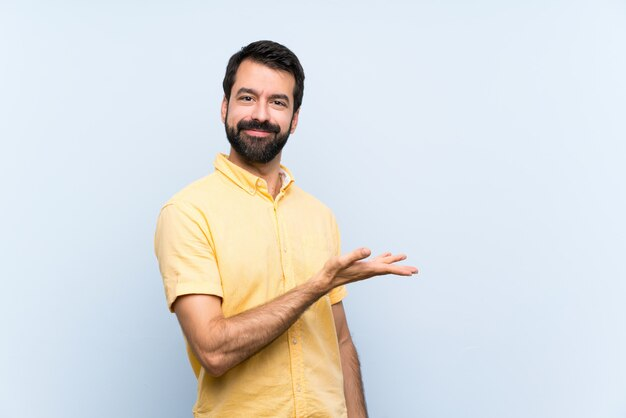 Jonge man met baard op blauw presenteren van een idee terwijl op zoek glimlachen naar