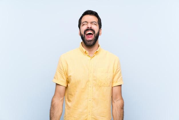 Jonge man met baard op blauw schreeuwen naar de voorkant met wijd open mond