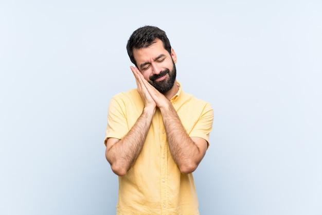 Jonge man met baard op blauw slaapgebaar in schattige uitdrukking
