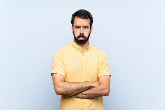 Jonge man met baard over geïsoleerde blauw met droevige en depressieve uitdrukking