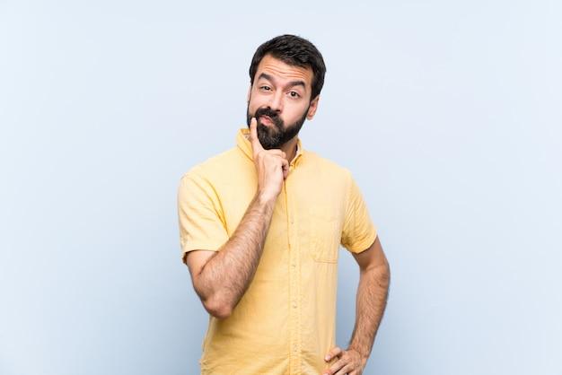 Jonge man met baard over geïsoleerde blauw op zoek naar voren