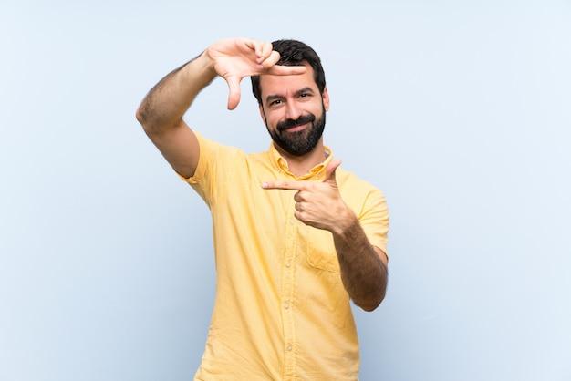 Jonge man met baard over geïsoleerde blauwe focus gezicht. framing symbool