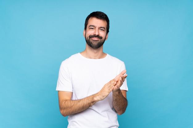 Jonge man met baard over geïsoleerde blauwe muur applaudisseren na presentatie in een conferentie