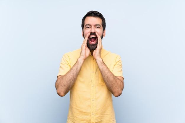 Jonge man met baard over geïsoleerde blauwe muur die en iets schreeuwt aankondigt