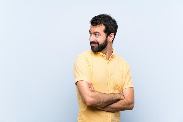 Jonge man met baard over geïsoleerde blauwe muur met gekruiste en gelukkige wapens