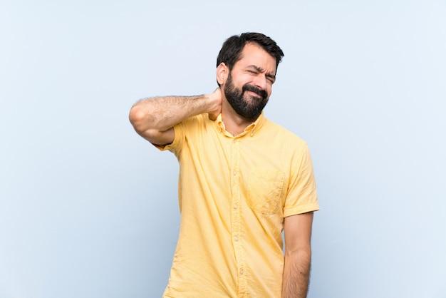 Jonge man met baard over geïsoleerde blauwe muur met nekpijn