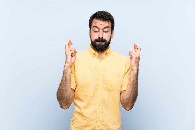 Jonge man met baard over geïsoleerde blauwe muur met vingers die en het beste kruisen wensen