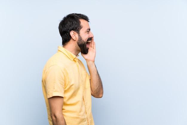Jonge man met baard over geïsoleerde blauwe muur schreeuwen met mond wijd open voor de zijtak