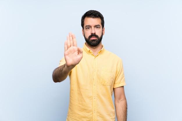 Jonge man met baard over geïsoleerde blauwe muur stop gebaar maken