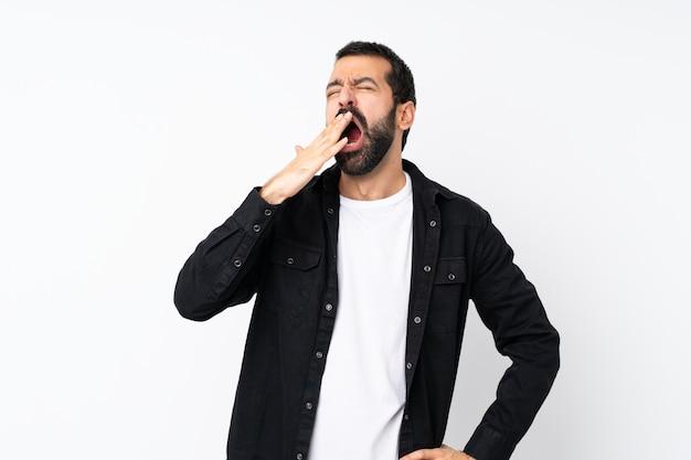 Jonge man met baard over geïsoleerde witte muur die en wijd open mond geeuwt met hand