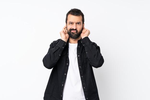 Jonge man met baard over geïsoleerde witte muur gefrustreerd en die oren bedekt