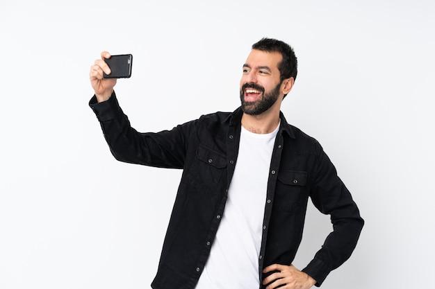 Jonge man met baard over geïsoleerde witte muur maken van een selfie