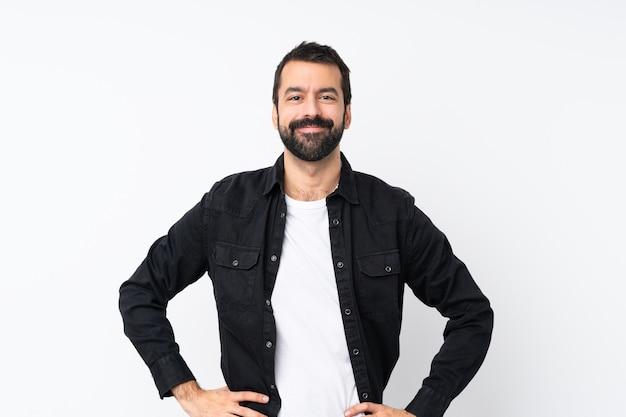 Jonge man met baard over geïsoleerde witte poseren met armen op heup en glimlachen