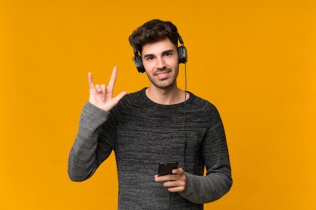 Jonge man met behulp van de mobiele telefoon met koptelefoon en zingen