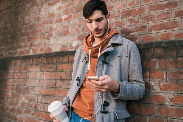 Jonge man met behulp van de mobiele telefoon.