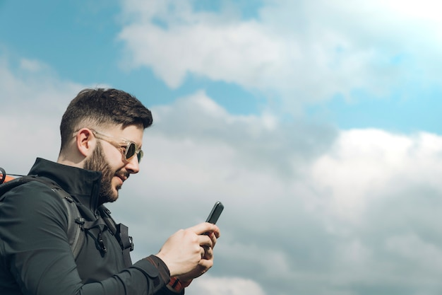 Jonge man met behulp van de smartphone terwijl in de natuur loopt