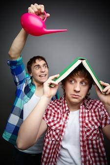Jonge man met behulp van een boek als een paraplu