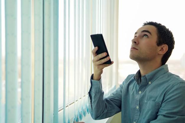 Jonge man met behulp van een smartphone voor een raam. bedien verticale jaloezieën met je telefoon. een venster openen met een mobiele app. slimme woning. moderne technologie op kantoor.