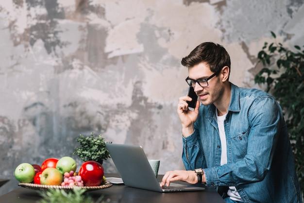 Jonge man met behulp van laptop en praten over mobilephone tegen verweerde muur