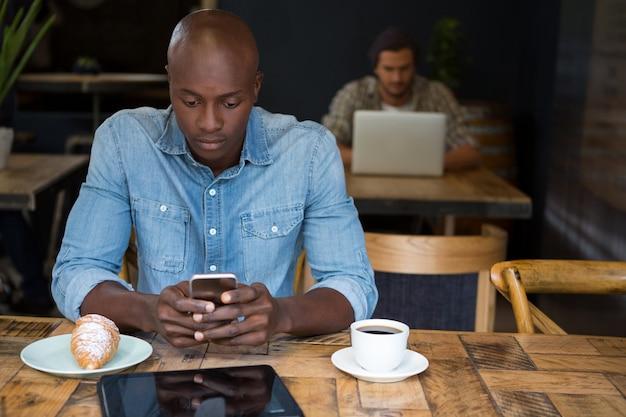 Jonge man met behulp van mobiele telefoon aan houten tafel in coffeeshop