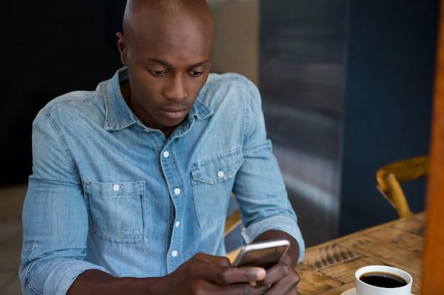 Jonge man met behulp van mobiele telefoon aan houten tafel in koffiehuis