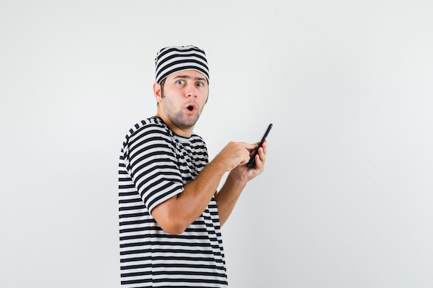 Jonge man met behulp van mobiele telefoon in t-shirt, hoed en verbaasd kijken.