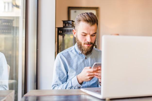 Jonge man met behulp van mobiele telefoon met laptop op bureau