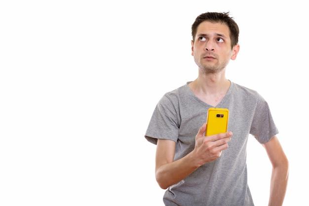 Jonge man met behulp van mobiele telefoon tijdens het denken
