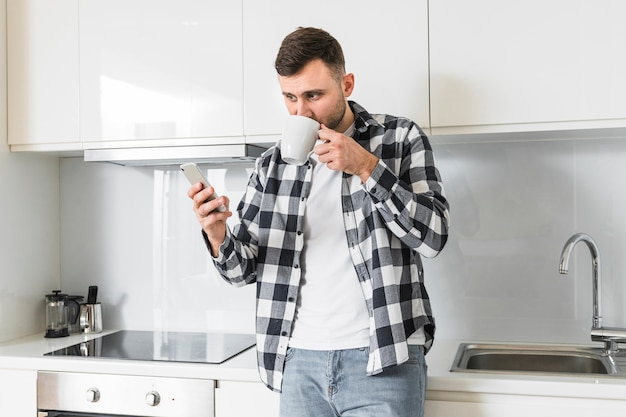 Jonge man met behulp van mobiele telefoon tijdens het drinken van de koffie in de keuken