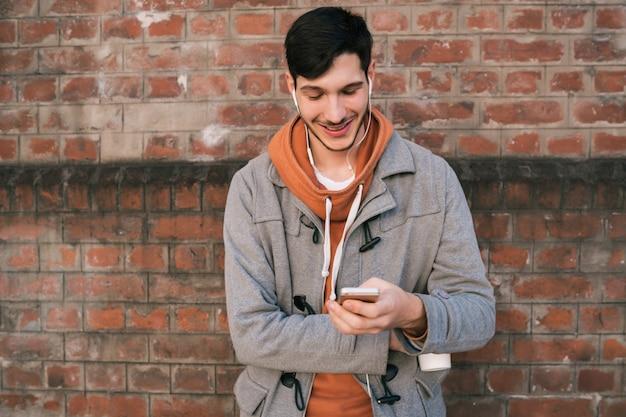 Jonge man met behulp van mobiele telefoon.