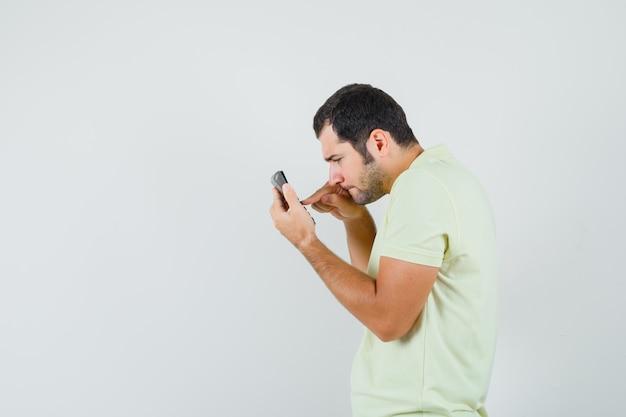 Jonge man met behulp van rekenmachine in t-shirt en op zoek naar serieus.