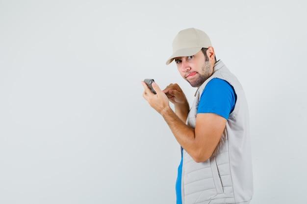 Jonge man met behulp van rekenmachine, tong uitsteekt in t-shirt, jasje en peinzend op zoek.