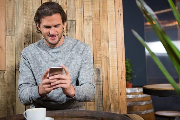 Jonge man met behulp van slimme telefoon aan tafel in de coffeeshop
