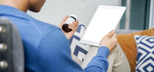 Jonge man met behulp van tablet naar video conference call met gespecialiseerde arts