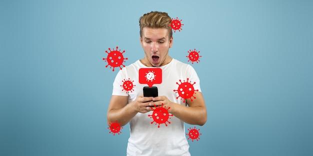 Jonge man met behulp van telefoon, kijken naar nieuws over de verspreiding van coronavirus en wereldwijde gevallen